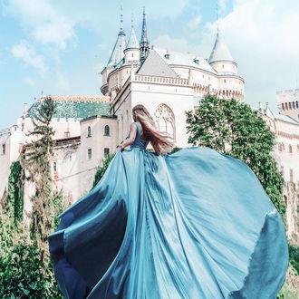 Фото Девушка в голубом платье стоит на фоне замка, by Jovana Rikalo