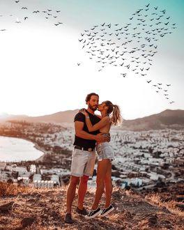 Фото Девушка целует парня, влюбленные стоят на фоне городка у моря, by anna_ix_