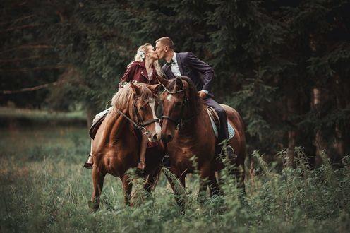 Фото Парень с девушкой целуются, сидя на лошадях. Фотограф Ieva Vogulienе