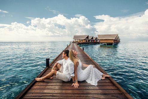 Фото Парень и девушка сидят на деревянном мосту, ведущему к домикам над морем. Фотограф Alexei Vladimir