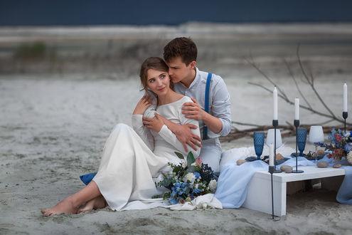 Фото Влюбленный парень нежно обнимает любимую девушку, оба сидят на песке у моря, фотограф Бармина Анастасия
