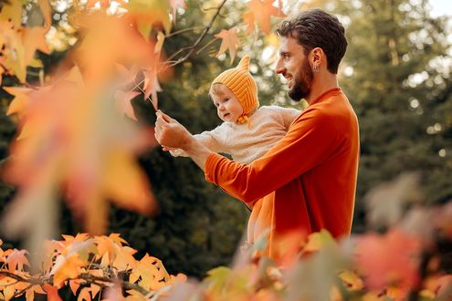 Фото Молодой папа с ребенком на руках стоит под ветвями осеннего дерева. Фотограф Дарья Адамова