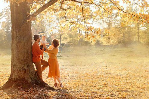 Фото Папа с ребенком на руках и мама стоят у осеннего дерева. Фотограф Дарья Адамова