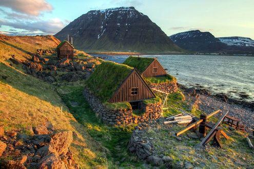 Фото Хижины, с покрытой зеленью крышей на фоне моря и гор и неба с облаками, Исландия