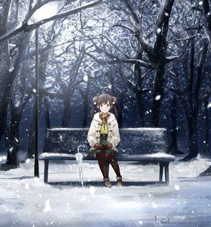 Фото Девочка сидит на лавочке в зимнем парке
