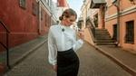 Фото Девушка в белой блузе и черной юбке стоит на дороге. Фотограф Georgy Chernyadyev