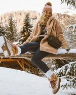 Фото Радостная девушка в шапочке и меховой куртке сидит на фоне снежной природы
