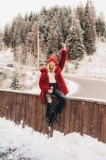 Фото Радостная девушка сидит на заборе с поднятой вверх рукой