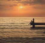 Фото Девушка сидит на краю мостика у моря. Фотограф Мария Трещева