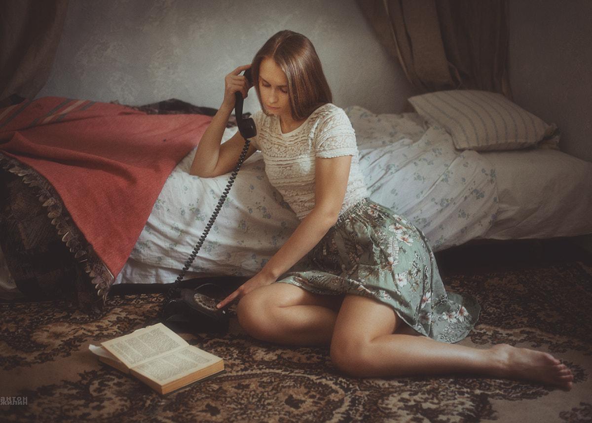 Фото Девушка сидит на полу с телефонной трубкой в рке на полу у кровати, by Anton Zhilin