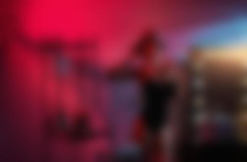 Фото Девушка в шляпе, бусах и черном боди позирует в комнате с розовым освещением, фотограф Георгий Дьяков