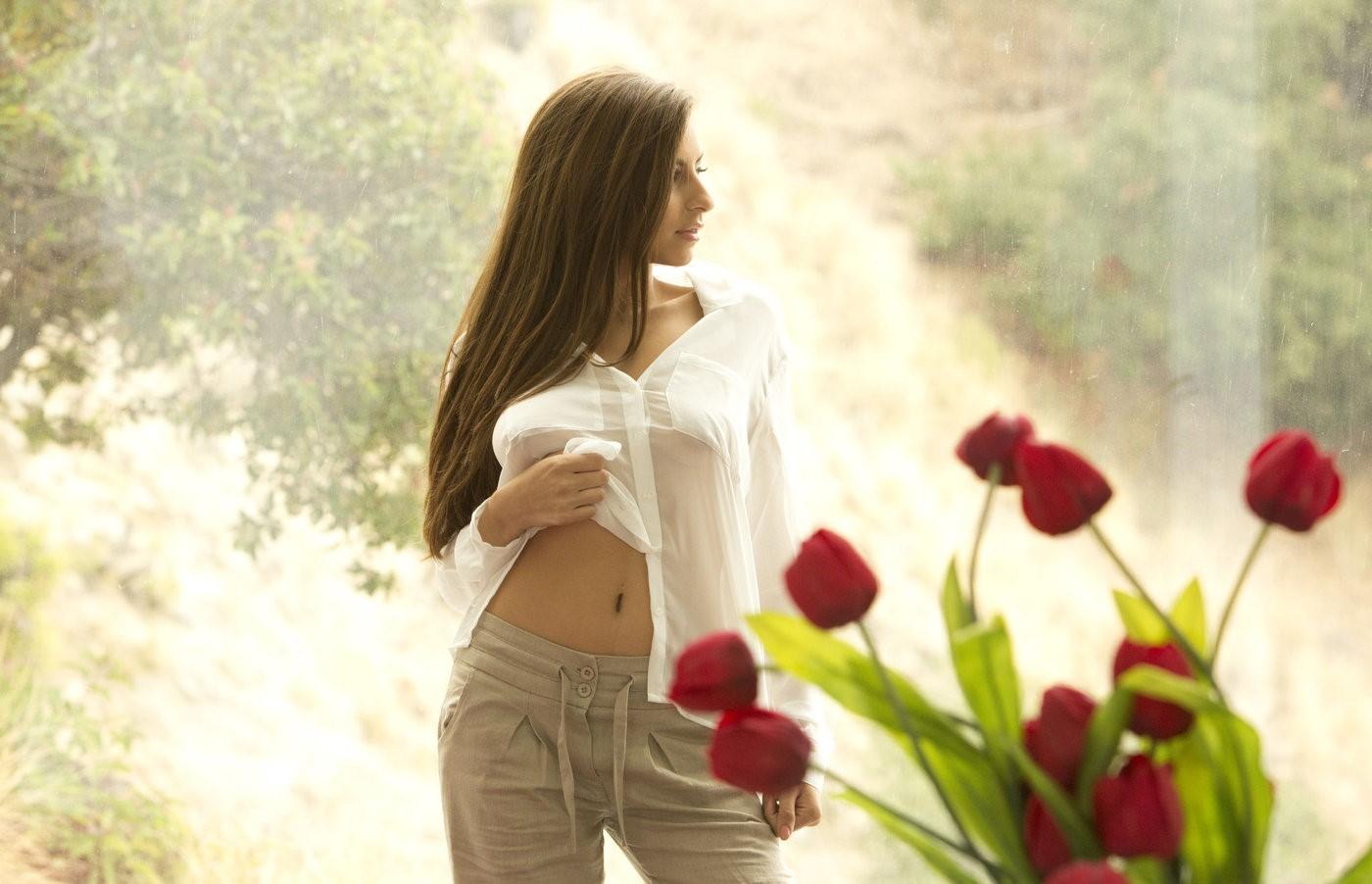 Фото Девушка смотрит в сторону, на переднем плане красные тюльпаны
