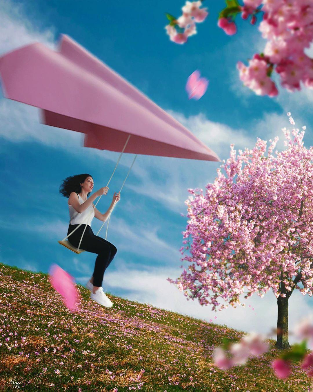 Фото Девушка на качели, подвешенной к бумажному самолету на фоне облачного неба и весеннего дерева, by Merve Keskin