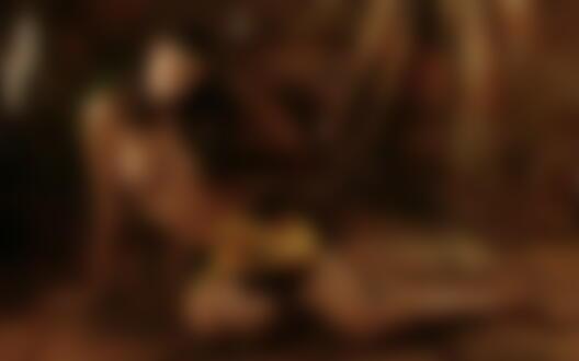 Фото Обнаженная девушка сидит на полу в студии оперевшись на руку у кресла