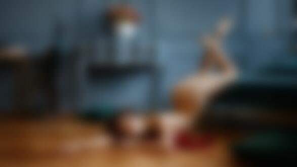 Фото Обнаженная модель Ника лежит на полу, а ножки ее подняты и лежат на кровати, фотограф Георгий Чернядьев