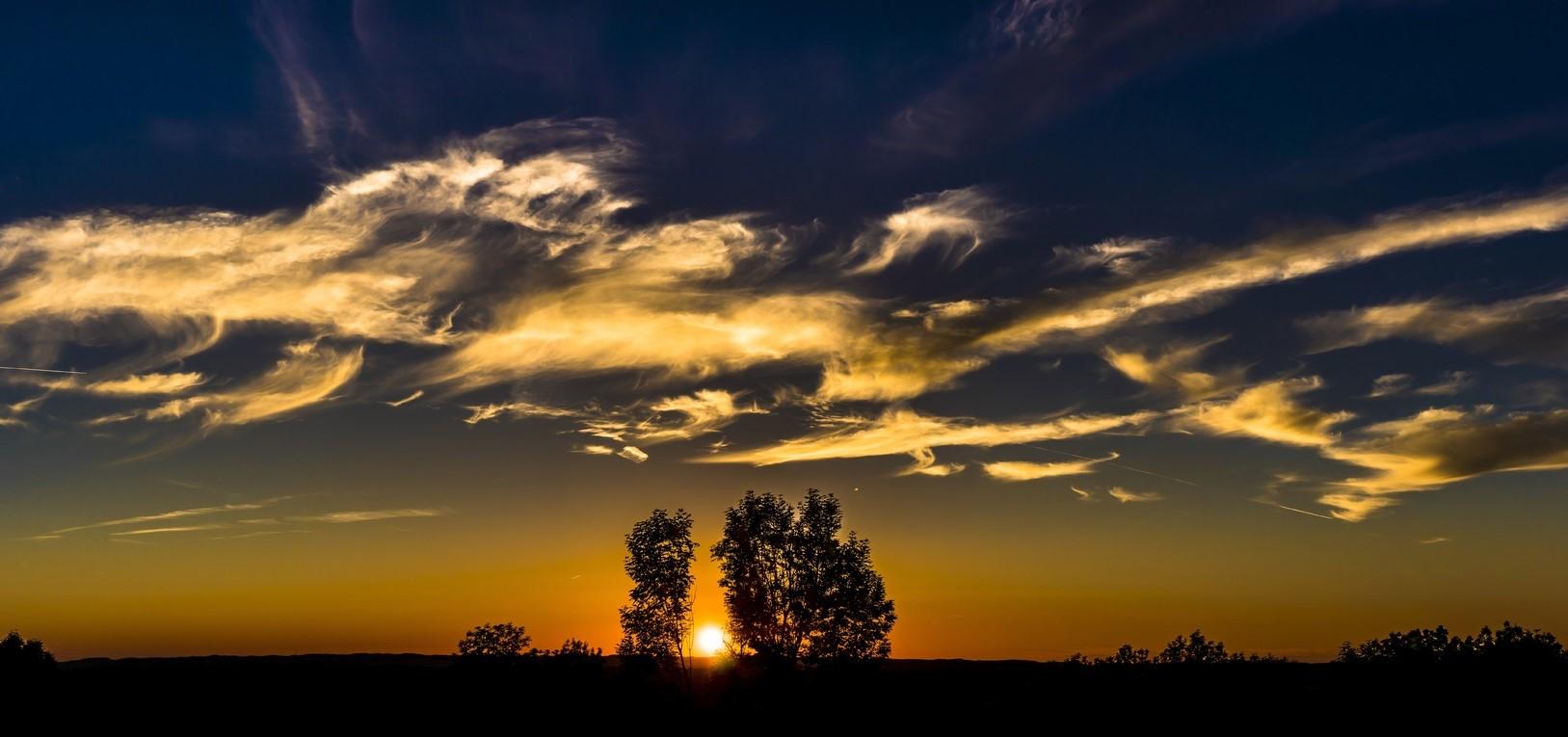 Фото Облака на небе и солнце на закате между деревьями