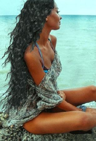 Анимация Жгучая брюнетка сидит на берегу и смотрит на море
