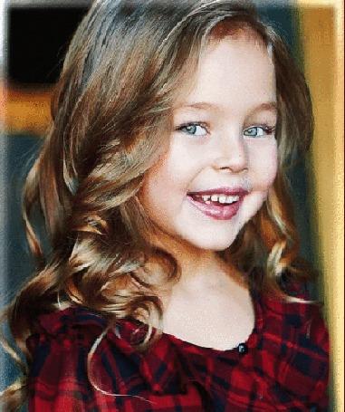 Анимация Милая девочка с распущенными волосами, голубыми глазами, с улыбкой на лице, в красном клетчатом платье