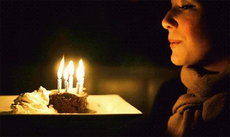 Анимация Женщина сидит перед тортом со свечами, которые она должна задуть, загадав желание