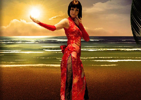 Анимация Девушка в восточном платье с разрезами на бедрах, стоит на фоне колышущего волнами моря и держит на вытянутой руке Солнце
