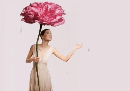 Анимация Девушка стоит под розовым цветком, укрываясь от капель дождя