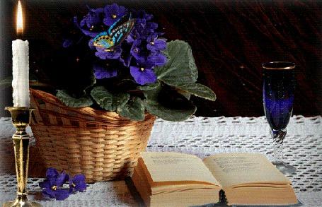 Анимация На столе лежит раскрытая книга, стоит корзинка с синими цветами, на которых сидит голубая бабочка, стоит подсвечник с зажженной свечой, стоит синего стекла фужер с шампанским