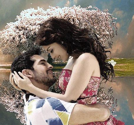 Анимация На фоне цветущих деревьев и реки мужчина поднял девушку, которая обняла его за шею