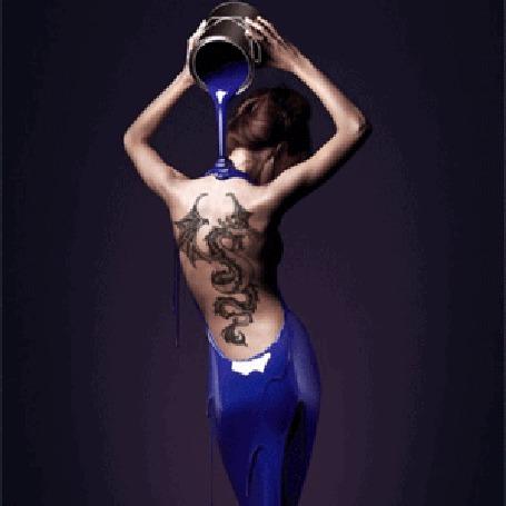 Анимация Девушка стоит к нам спиной и, подняв руки над головой, выливает себе на спину синюю краску из ведерка. На открытую спину девушки нанесено тату. Синяя тонкая ткань прикрывает тело девушки ниже пояса