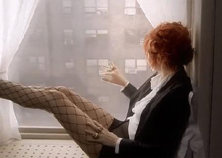 Анимация Девушка сидит на подоконнике, смотрит в окно и рисует пальцем руки фигуры на стекле