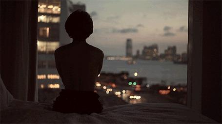 Анимация Девушка сидит на фоне ночного города
