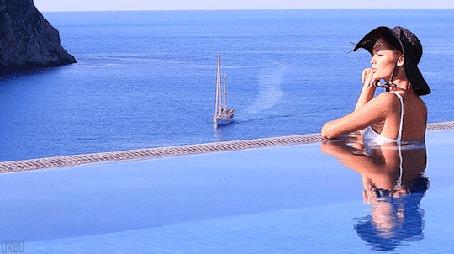 Анимация Девушка в шляпе, сидит в бассейне, смотря в сторону, на фоне моря и парусника (© Seona), добавлено: 06.05.2015 14:09