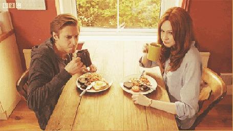 Анимация Рори / Rory и Эми / Amy из сериала Доктор кто / Doctor who сидят за обеденным столом, держат в руках чашки с напитком и приветствуют поднятием чашек вверх (© Akela), добавлено: 08.05.2015 15:14