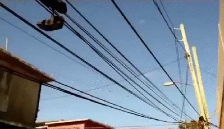 Анимация Пара мужских кроссовок сиротливо болтающаяся на проводах линии электропередач, на фоне голубого неба и крыш домов (© Георгий Тамбовцев), добавлено: 13.05.2015 18:35