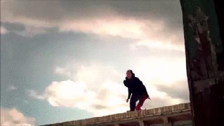Анимация Полет мужчины между крышами домов, на фоне облачного неба