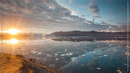 Анимация Море в солнечных лучах, птицы летящие над водой, островок, горы виднеющийся вдали, льдинки в солнечном отблеске, небо, вода.(1600Х900)