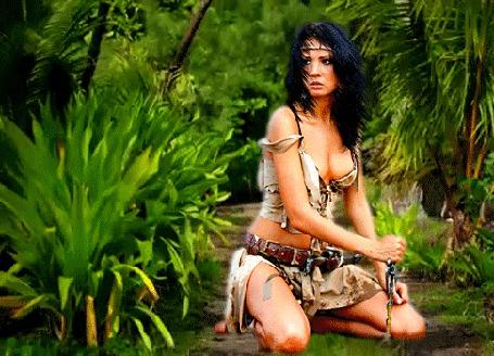Анимация Девушка амазонка стоит на коленях в тропическом лесу и держит в руке кинжал, ветер треплет ее черные волосы