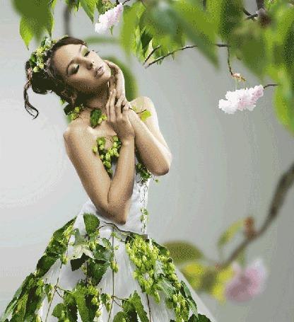 Анимация Меняющееся изображение девушки в платье с зелеными листьями, стоящей под деревом с зазеленевшими ветками и белыми цветами