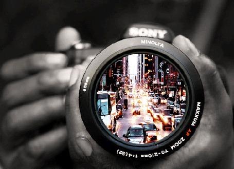 Анимация Мужчина держит в руках фотоаппарат, в котором видно движение авто по городским улицам