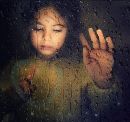 Анимация Девочка за стеклом в каплях от дождя, рисует пальчиком на стекле сердечко