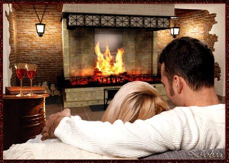 Анимация Вечер, в комнате горит огонь в камине, на диване сидят обнявшись мужчина и девушка, рядом на тумбочке стоят два бокала с вином (© ДОЛЬКА), добавлено: 25.06.2015 02:31