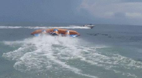 Анимация Забавный аттракцион, надувной катамаран, идущий за катером, поднимается над волнами