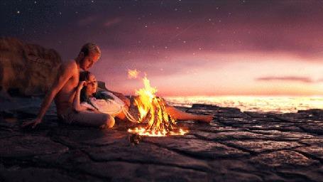 Анимация Влюбленные лежат на берегу моря и смотрят на огонь