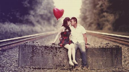 Анимация Девушка с воздушным шариком в руке сидит на плите качая ножкой рядом с парнем