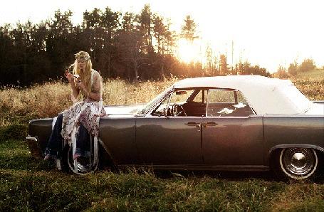 Анимация На фоне неба, леса, среди поля стоит машина, на капоте сидит девушка и гадает на цветке