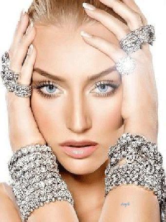 Анимация Женщина с голубыми глазами трогает свое лицо руками, на них браслеты из бриллиантов, а на пальцах кольца с драгоценными камнями