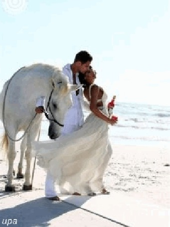 Анимация Мужчина прижимается к женщине, которая держит в руке бутылку вина, около них стоит красивый белый конь, а их взгляду открываются голубое небо и теплое море, upa