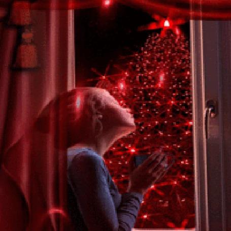 Анимация Девушка с чашкой смотрит на елку за окном