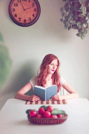 Анимация Девушка за столом читает книгу и смотрит в окно