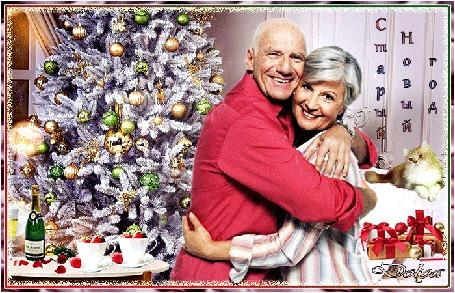Анимация У елки, обнявшись стоят мужчина и женщина, рядом лежат новогодние подарки, стоит стол, на котором стоит шампанское, розы и чашки с клубникой (Старый Новый год), by ДОЛЬКА