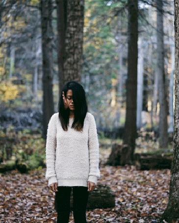 Анимация Девушка стоит на фоне деревьев, на ее лице чья-то рука
